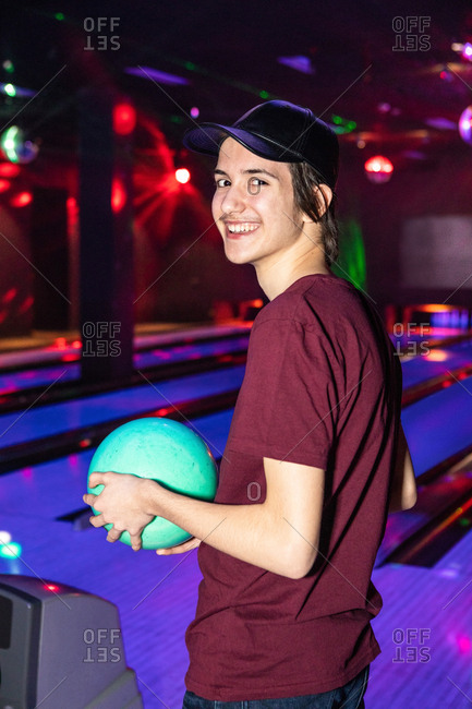 Portrait of smiling teenage boy holding ball at bowling alley