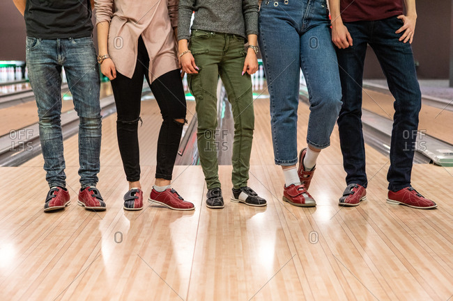 Low section of multi-ethnic friends standing on parquet floor at bowling alley
