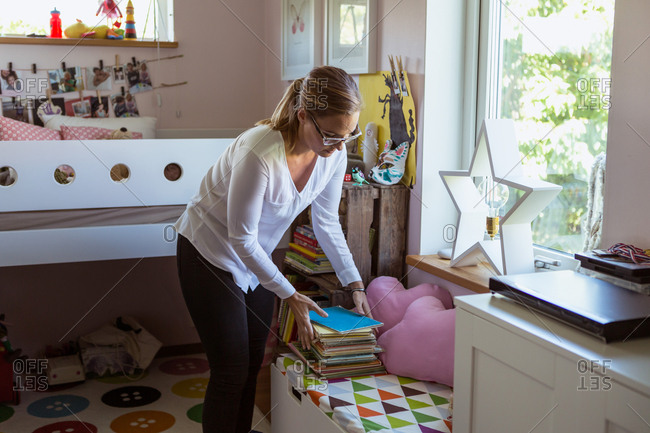 Woman stacking books on table while cleaning bedroom at home