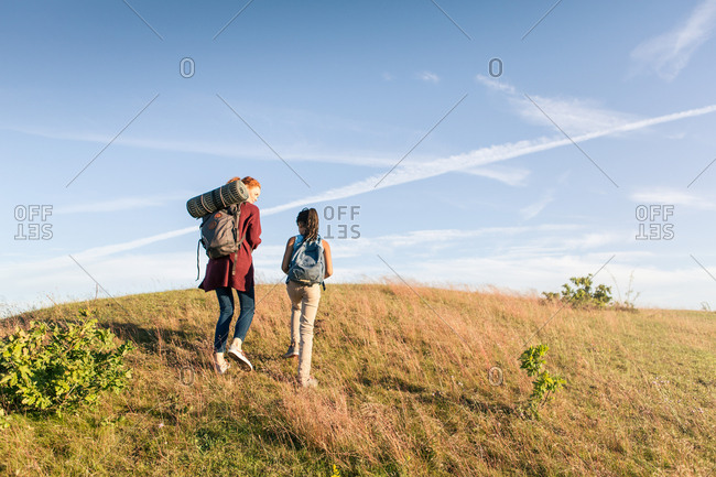 Low angle view of mother and daughter moving uphill at park against blue sky