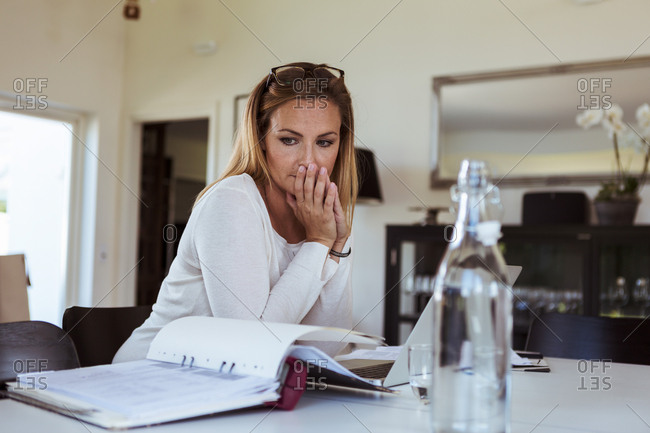 Tensed woman looking at bills while sitting at table in living room