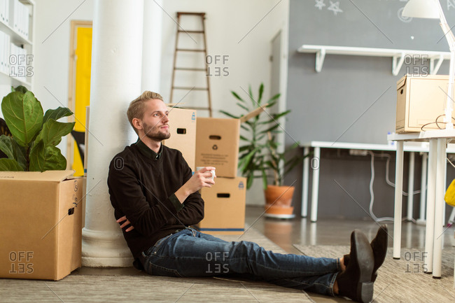 Full length of thoughtful young businessman with coffee cup sitting on floor at creative office