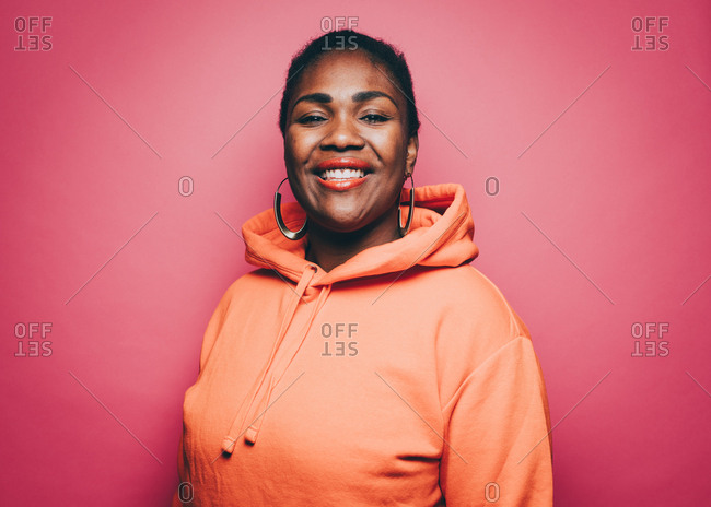 Portrait of smiling mid adult woman wearing orange hooded shirt over pink background