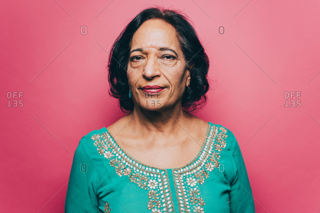 Portrait of confident senior woman with black short hair over pink background
