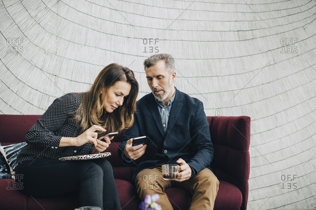 Businessman and woman using mobile phones while sitting on couch during conference