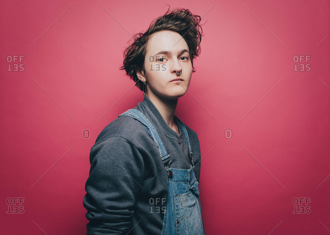 Portrait of confident male hipster standing against pink background