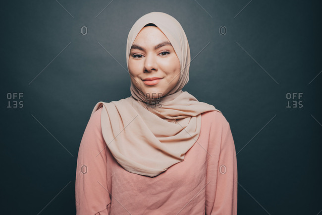 Portrait of smiling young woman wearing hijab against gray background
