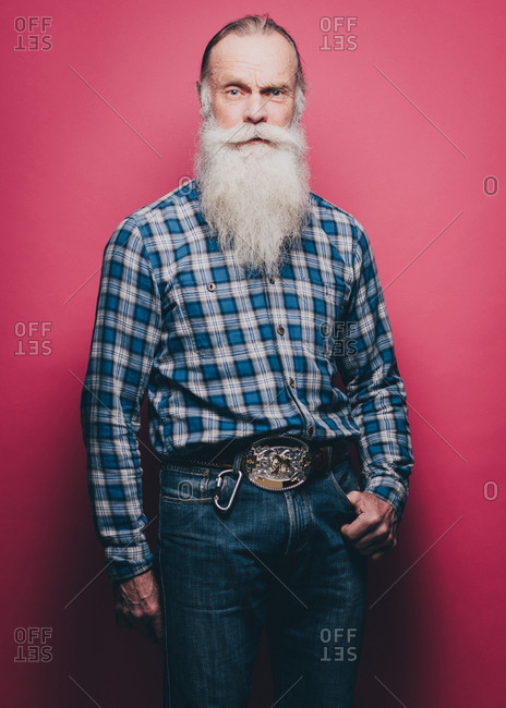 Full length portrait of confident senior man standing against pink background