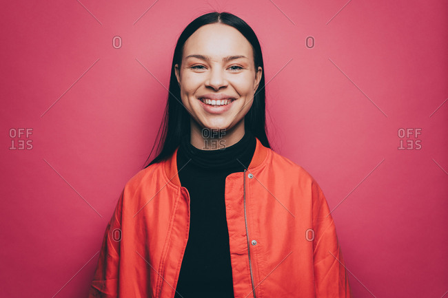 Portrait of smiling woman wearing orange jacket over pink background