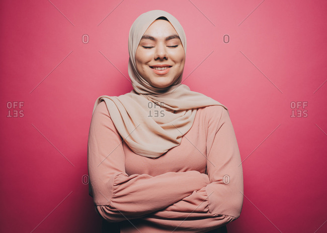 Smiling Muslim woman with eyes closed standing against pink background