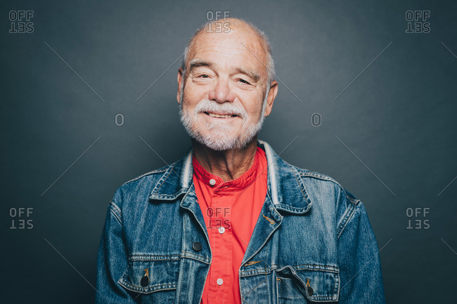 Portrait of smiling senior man wearing denim jacket against gray background