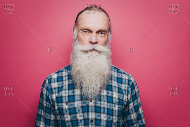 Portrait of confident senior man with long white beard against pink background