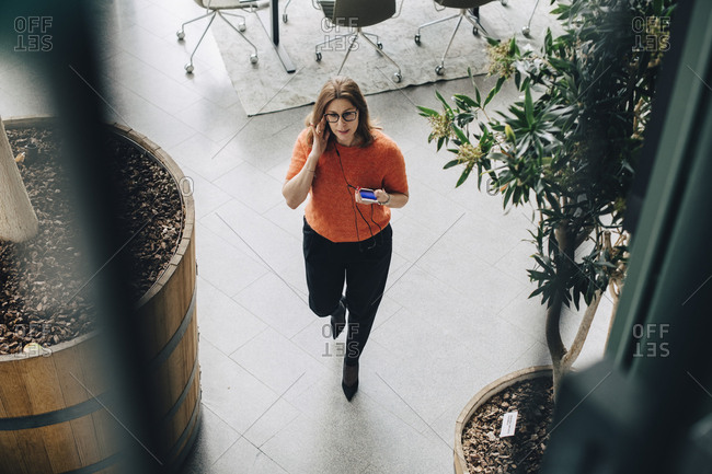 High angle view of businesswoman using mobile phone while walking in office