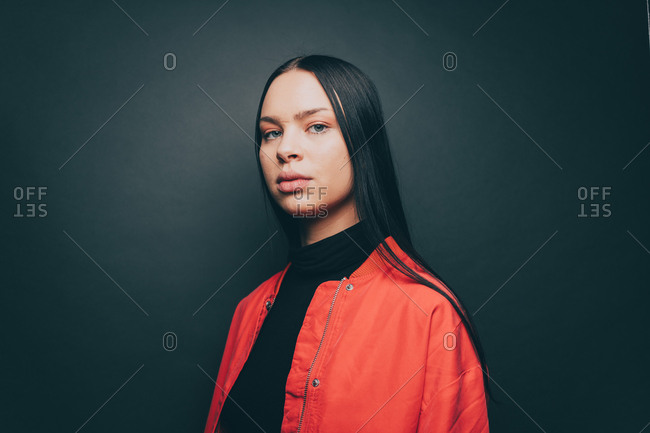 Portrait of woman wearing orange jacket over gray background