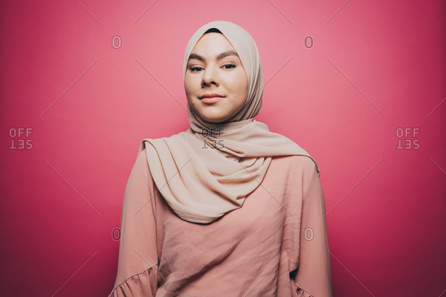Portrait of confident young woman wearing hijab against pink background