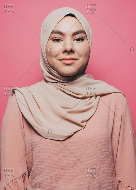 Portrait of smiling young woman wearing hijab against pink background