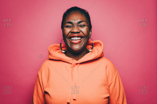 Cheerful mid adult woman wearing orange hooded shirt over pink background