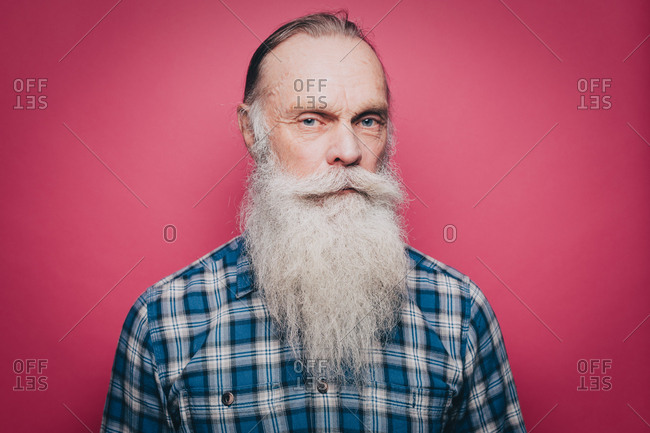 Portrait of serious senior man with long white beard against pink background