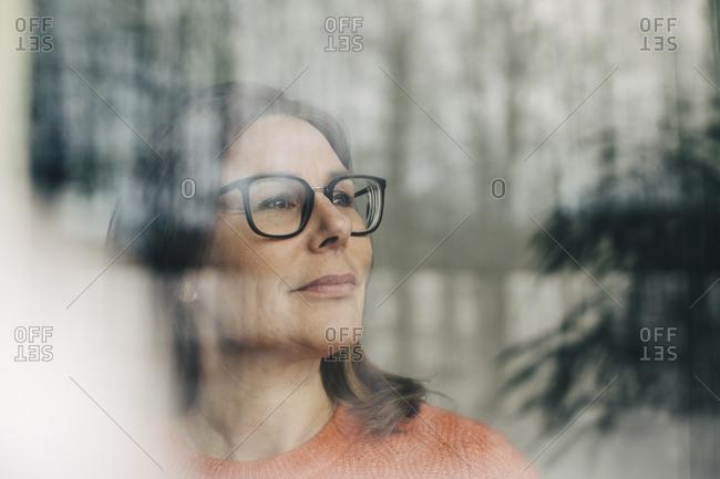 Close-up of thoughtful businesswoman wearing eyeglasses seen through window
