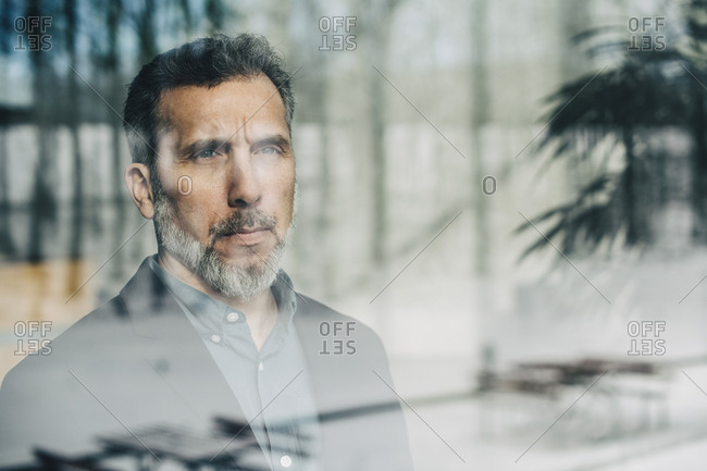 Close-up of thoughtful businessman seen through glass window at office