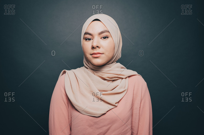 Portrait of confident young woman wearing hijab against gray background