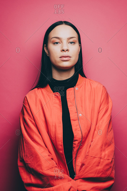 Portrait of confident woman wearing orange jacket over pink background