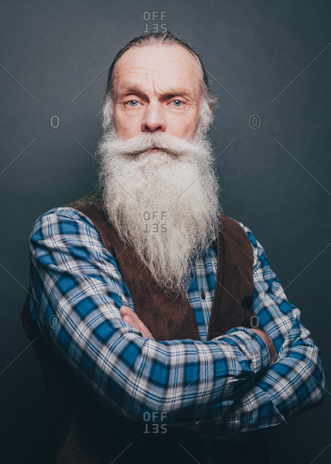 Portrait of confident bearded senior man standing arms crossed over gray background