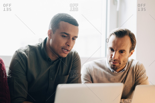 Confident multi-ethnic male coworkers discussing over laptop at creative office