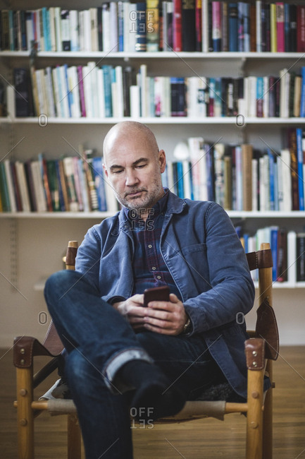 Confident mature therapist using mobile phone while sitting against bookshelf at home office