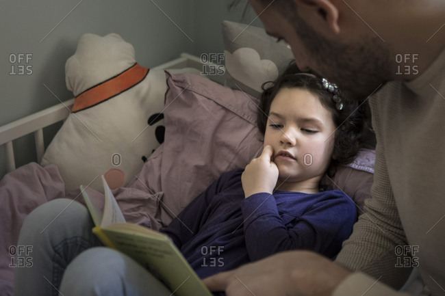 Father telling story while reading book to daughter on bed at home