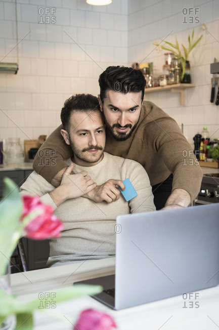 Homosexual couple doing online shopping through laptop in kitchen at home