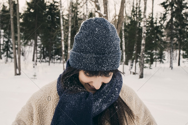 Smiling mid adult woman wearing knit hat and scarf during winter