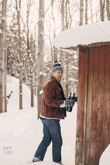 Smiling man holding drink container while walking by log cabin on snowy landscape