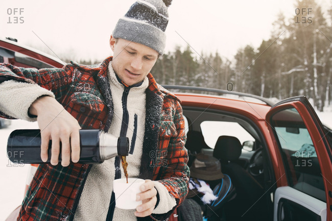 Mid adult man pouring coffee from insulated drink container while standing by car