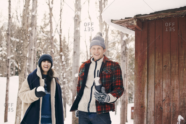 Portrait of happy friends holding snowball while standing by log cabin during winter