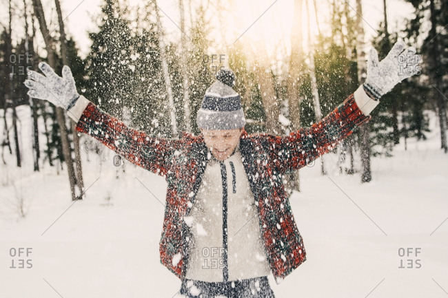Happy mid adult man playing with snow on snow covered field