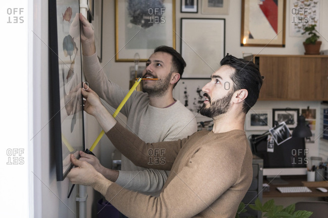 Young man with tape measure assisting partner while hanging painting on wall