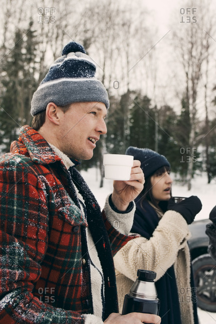 Smiling man standing with friend and having coffee during winter