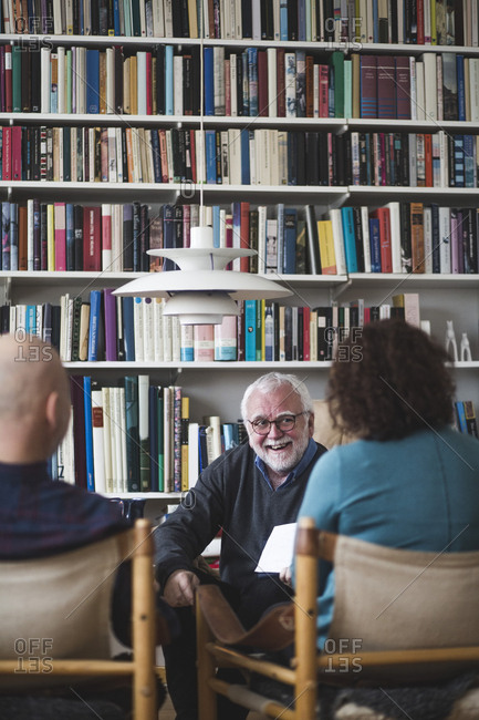 Smiling senior therapist explaining analysis to couple at home office