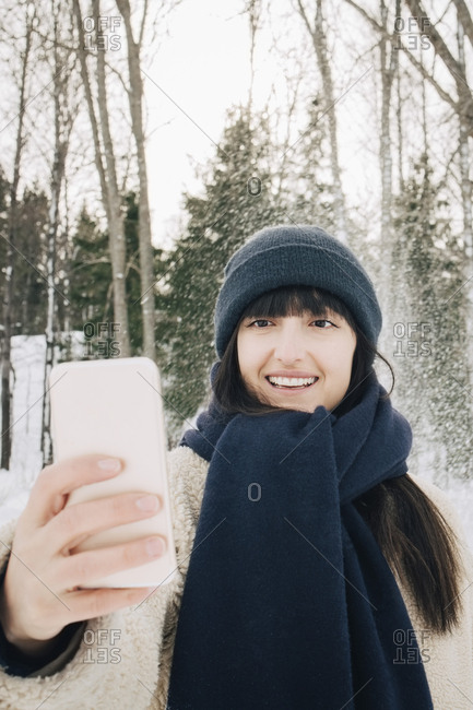 Smiling mid adult woman taking selfie through mobile phone during winter