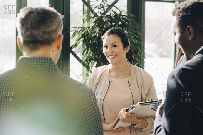 Smiling female entrepreneur discussing with male colleagues while standing in office