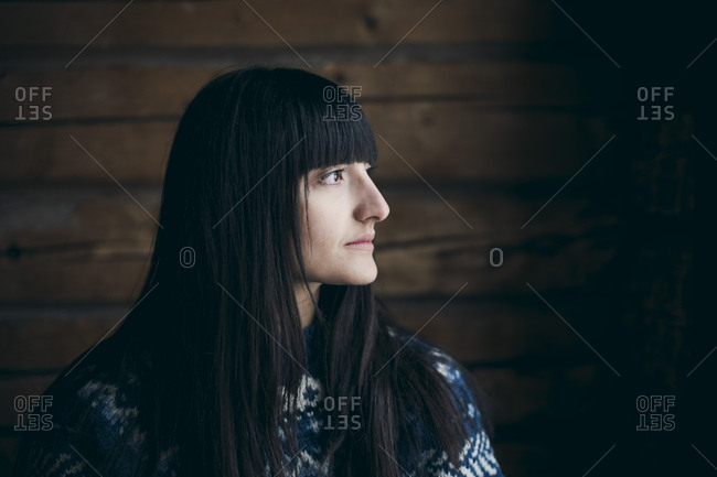 Close-up of thoughtful woman looking away at log cabin