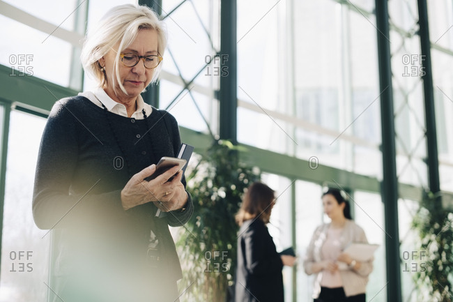 Senior businesswoman using mobile phone while colleagues communicating in background