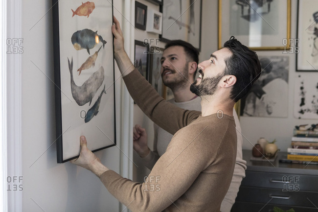Homosexual couple hanging painting on wall at home