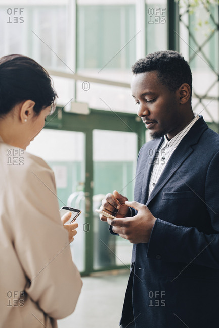 Male and female entrepreneurs using phones in meeting at office