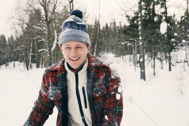 Portrait of happy mid adult man in warm clothing on snow covered field