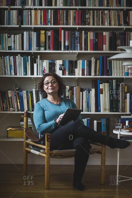 Portrait of female therapist holding digital tablet while sitting against bookshelf
