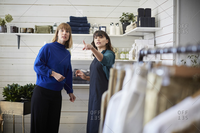 Female owner pointing and showing while communicating with customer at boutique