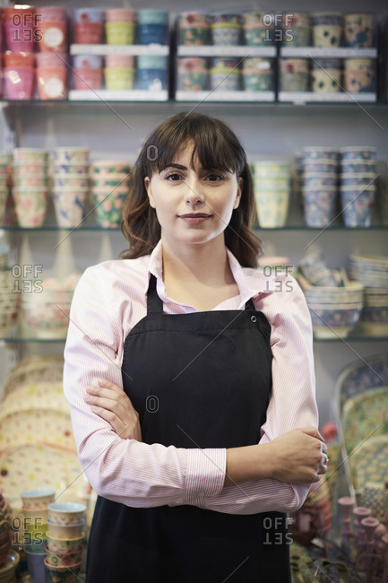 Portrait of confident female owner standing with arms crossed against multi colored crockery at store