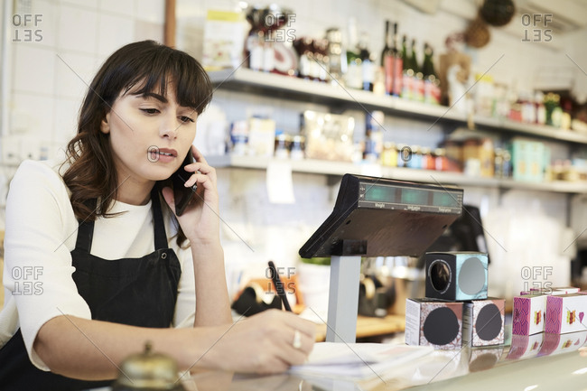 Female owner taking order through mobile phone at counter in store
